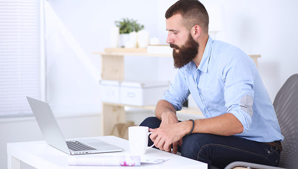 bigstock-Young-man-sitting-with-laptop-108959564