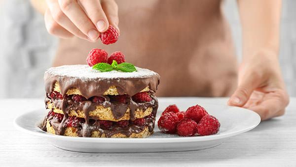 bigstock-woman-decorating-berry-cake-wi-144074426